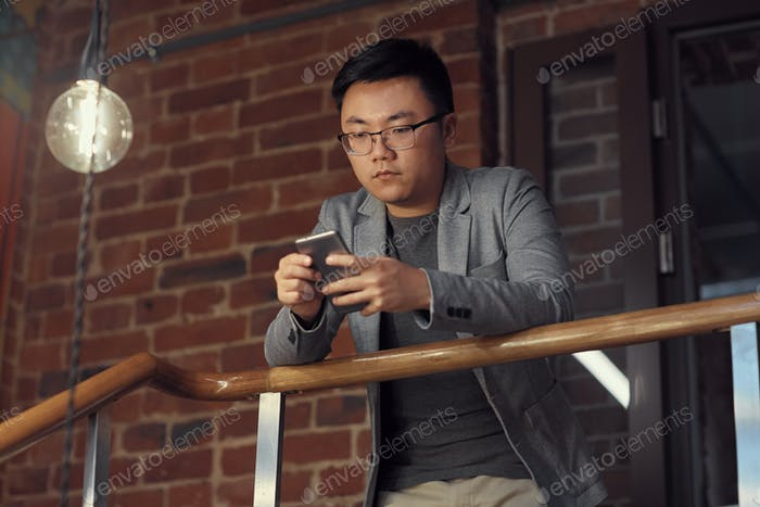 Asian Man using Smartphone at Balcony