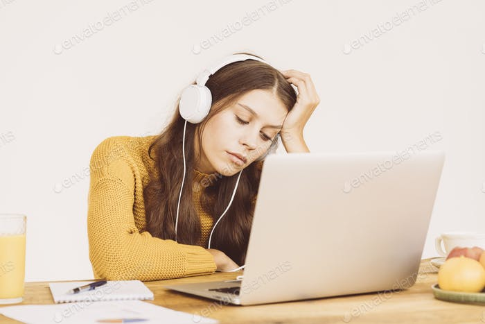 Young girl fell asleep in front of laptop. Cute woman is bored