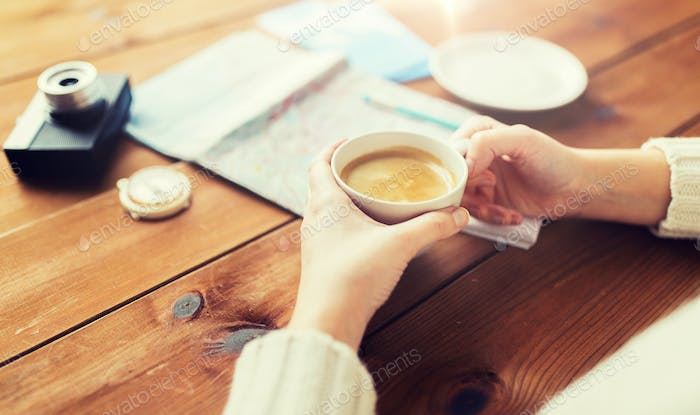 close up of hands with coffee cup and travel stuff