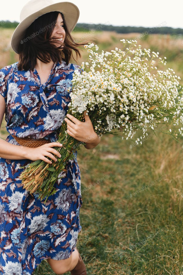 Stylish young woman in blue vintage dress and hat walking with white wildflowers in summer meadow