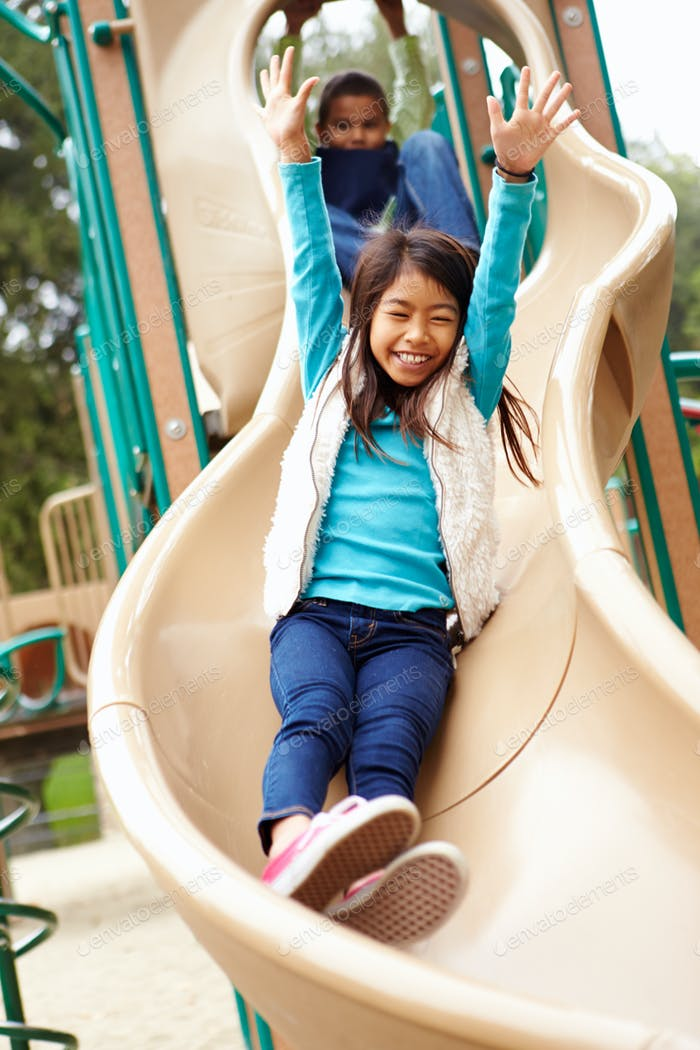 Young Girl Playing On Slide In Playground