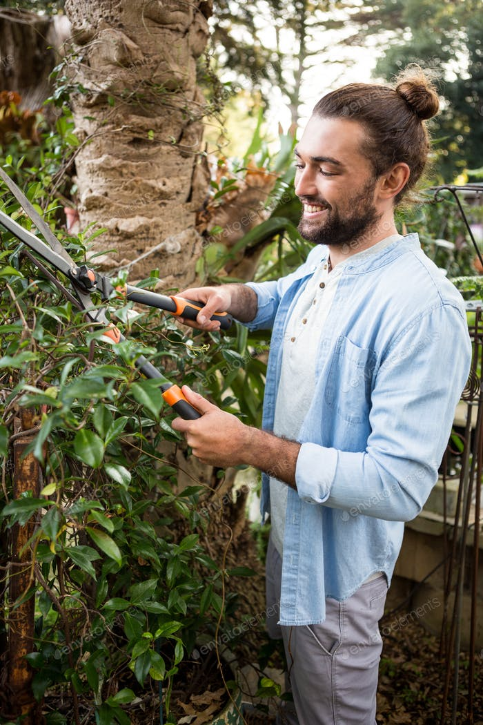 Happy worker using hedge clippers at garden