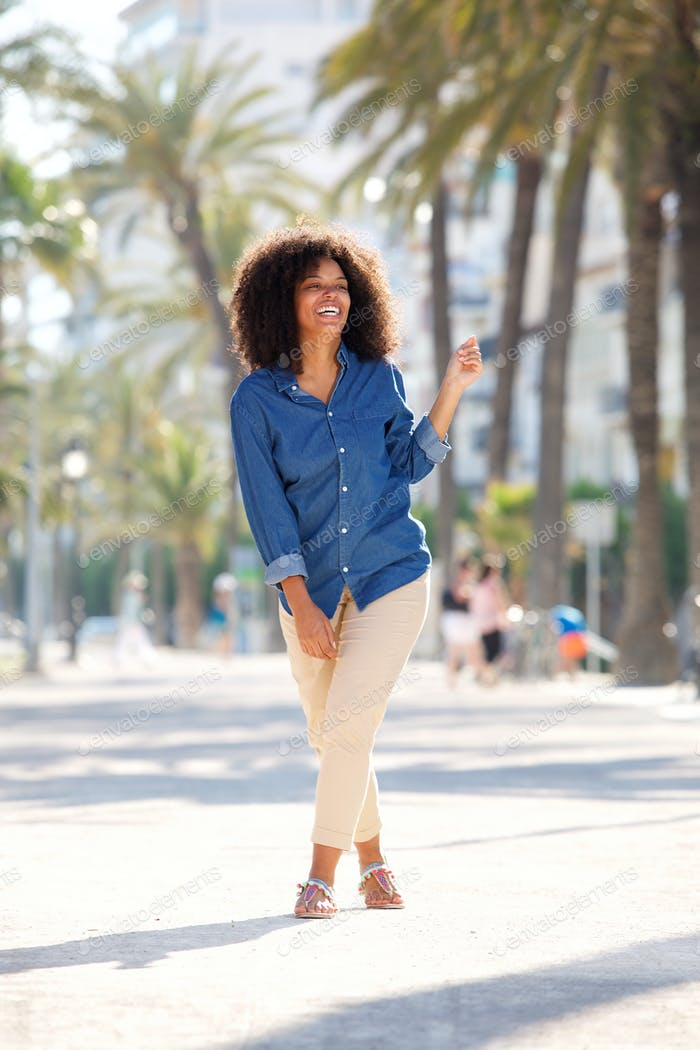 cheerful woman outside with palm trees in background