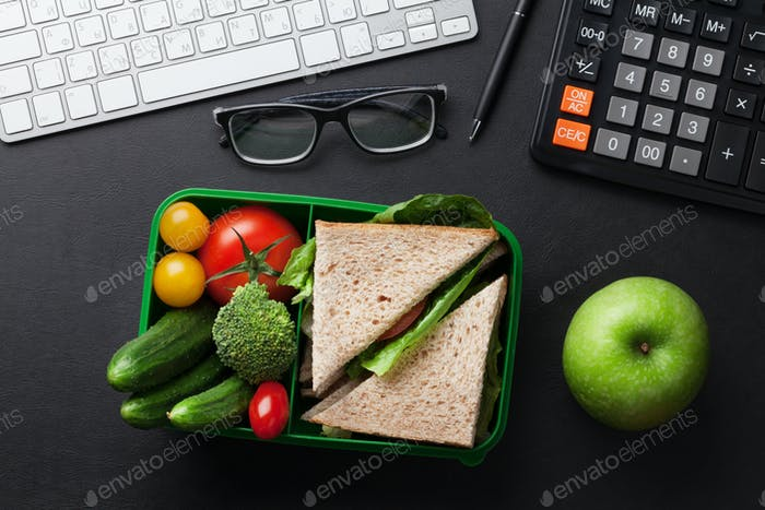 Office desk with supplies and lunch box