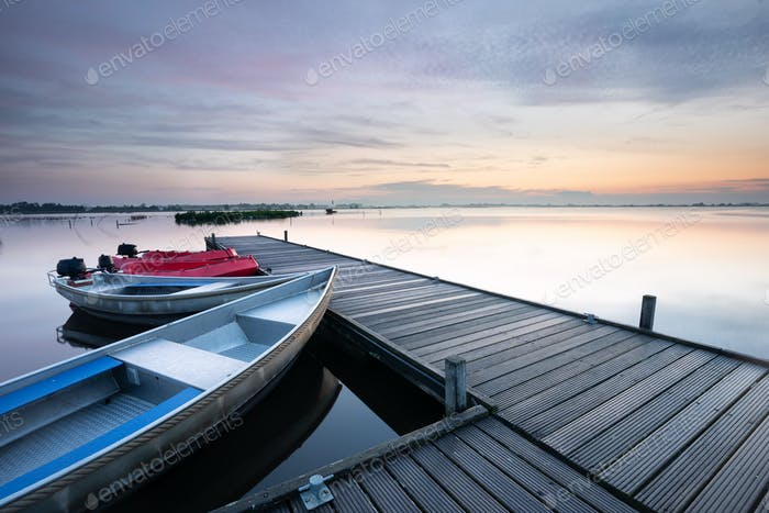 boat at pier on big lake during sunrise