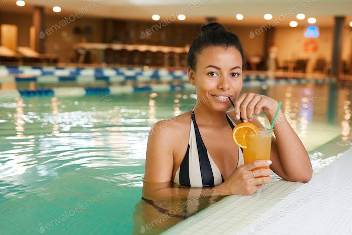 Mixed-Race Woman Enjoying Cocktails in Swimming Pool