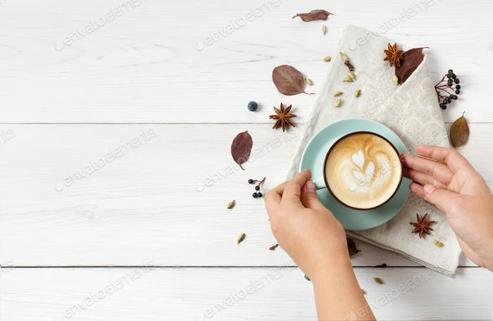 Woman has autumn cappuccino coffee, top view on white wood