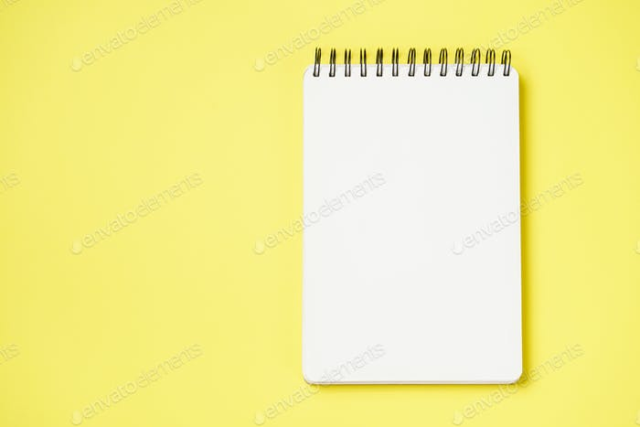 Spiral notebook on a yellow background