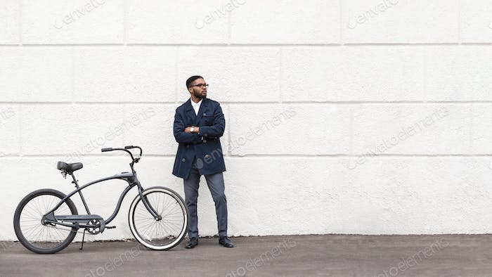 Handsome afro businessman posing with his bike