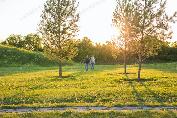 Pregnant woman with husband walking on meadow in the sunlight