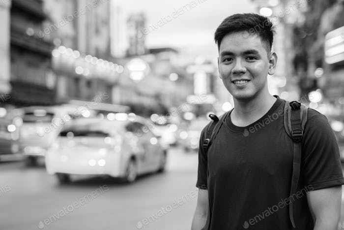Portrait of young handsome Asian tourist man exploring at Chinatown