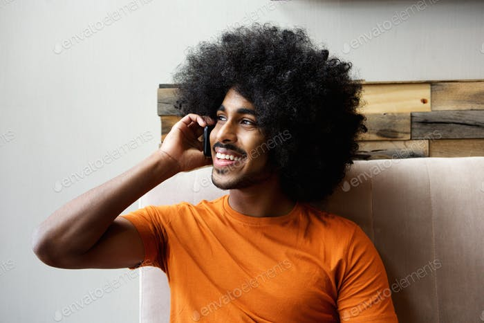 Happy black guy talking on mobile phone indoors