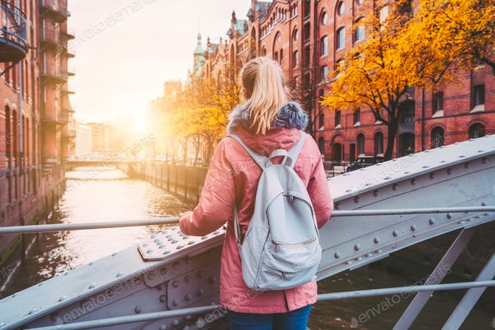 Back rear view of adult blond woman tourist with backpack enjoying autumn beautiful sunset scene on