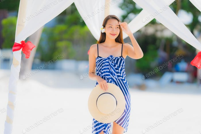 Portrait young asian woman smile happy around beach sea ocean wi