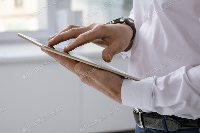 Hands of elegant businessman with tablet scrolling through online data