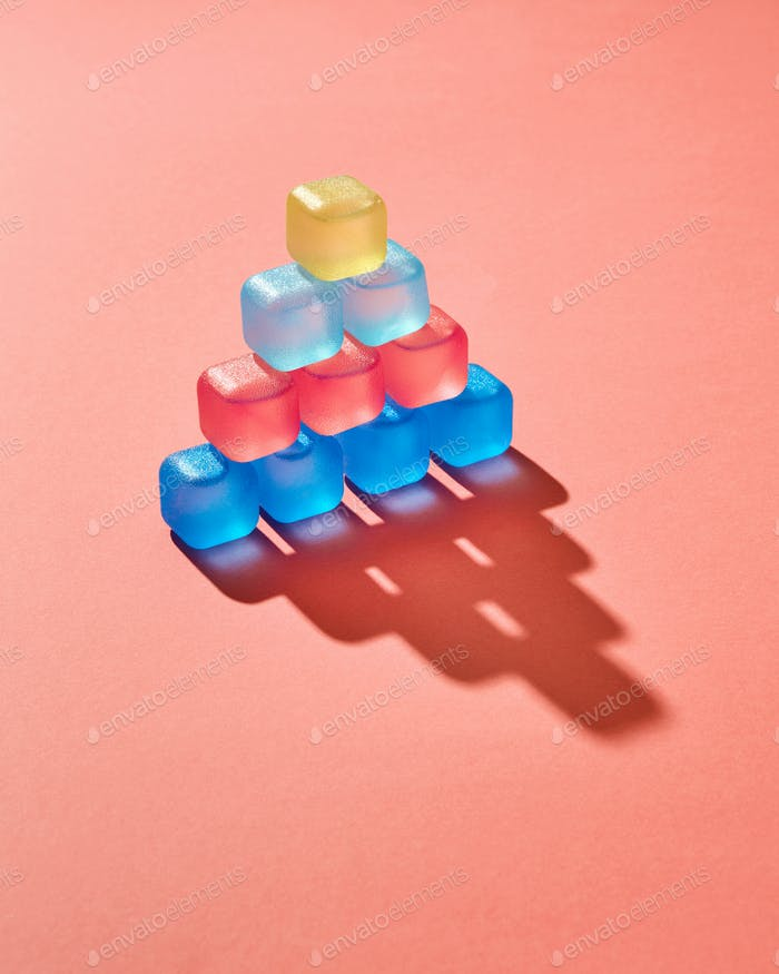 Creative pyramid from colored plastic cubes with liquid, shadows on a background in a color of the