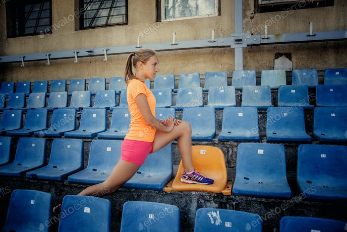 Sporty slim woman in pink shorts and orange shirt.