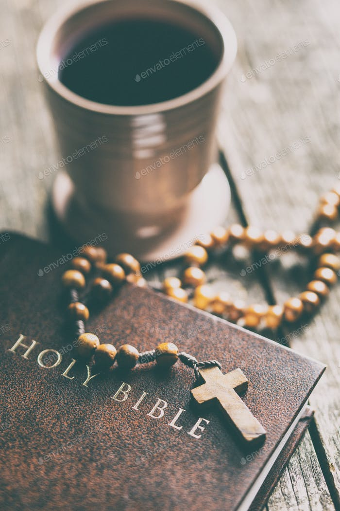Rosary beads, holy bible and cup of wine.
