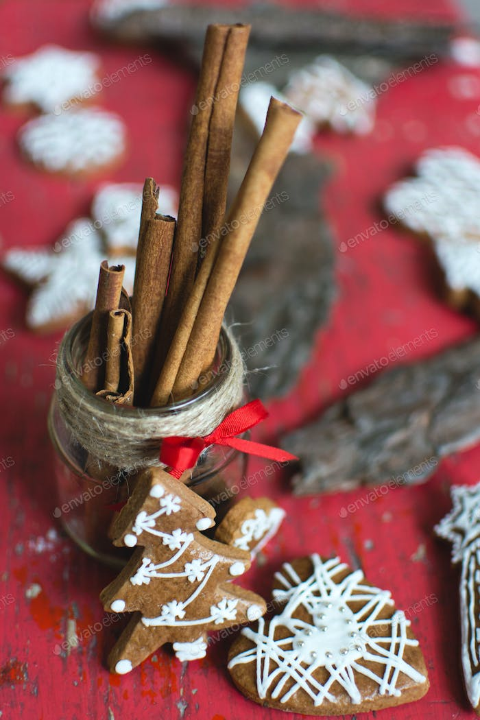Bunch of traditional Christmas gingerbread with icing on a red wooden background