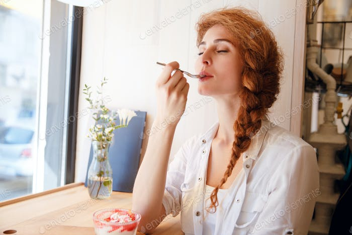 Attractive happy young woman sitting and enjoy eating dessert