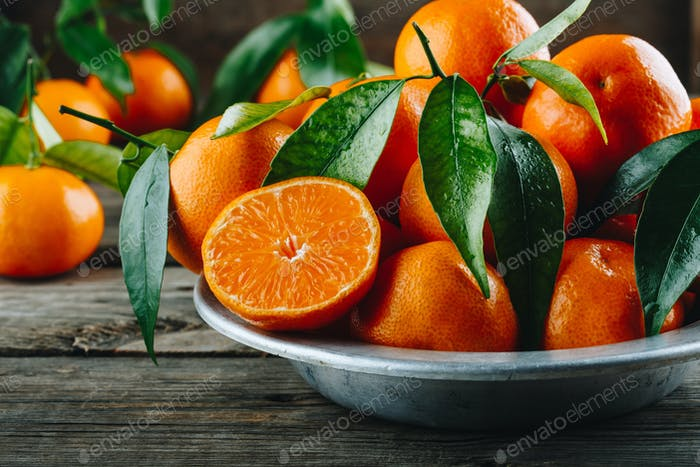 Fresh Clementine Mandarin Oranges fruits or Tangerines with leaves on wooden background
