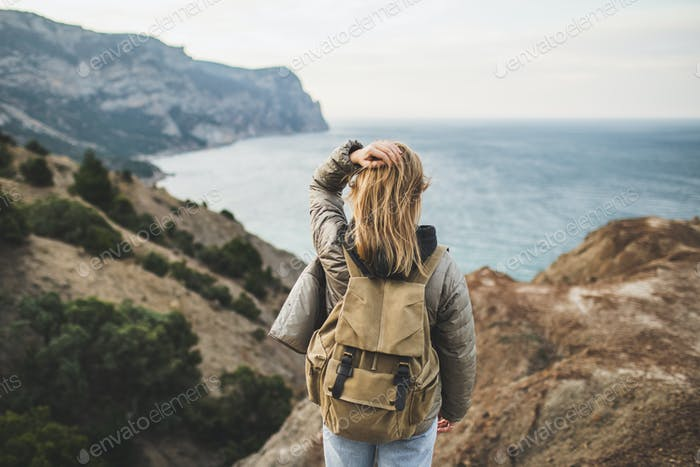 Backpacker hippie woman happy to enjoy amazing sea and mountain view from hill. View from behind