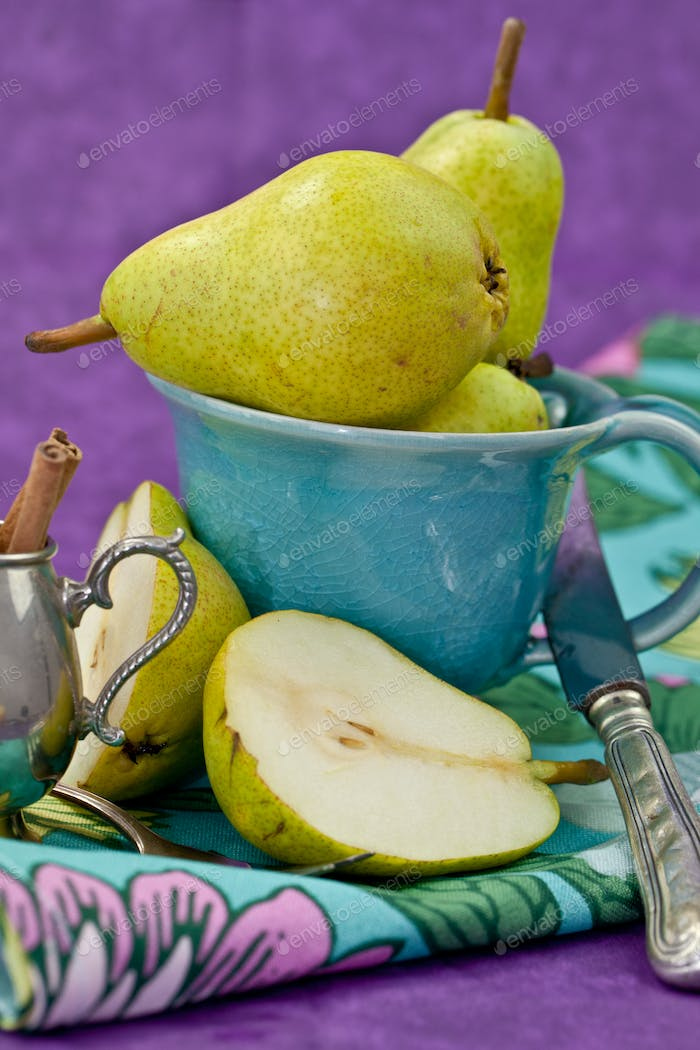 Fresh pears in a vintage blue cup