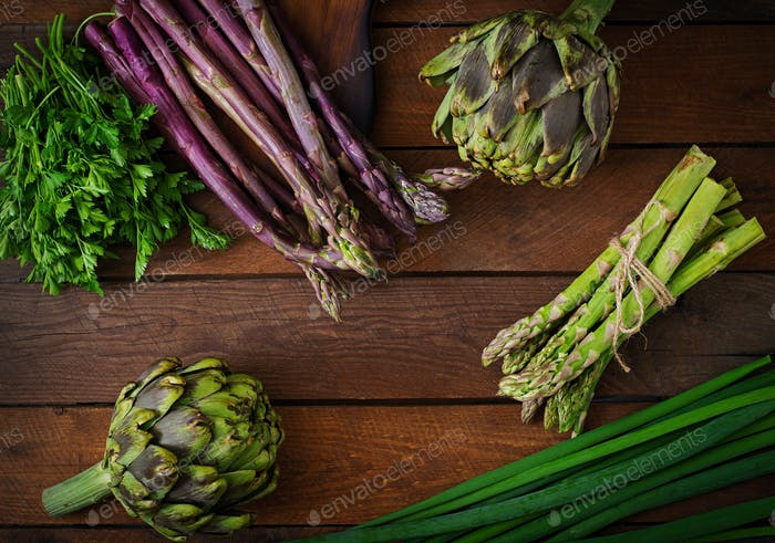 Asparagus and artichokes with herbs on a wooden background. Top view