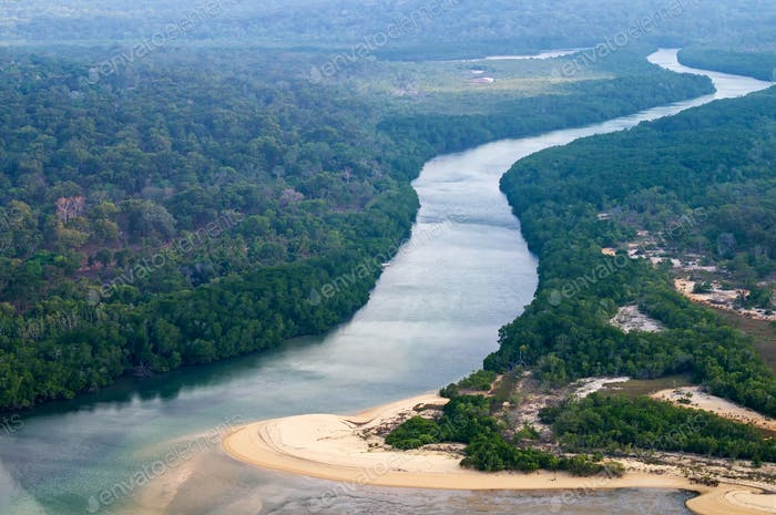 Aerial view to the ocean coast, river and rainforest.