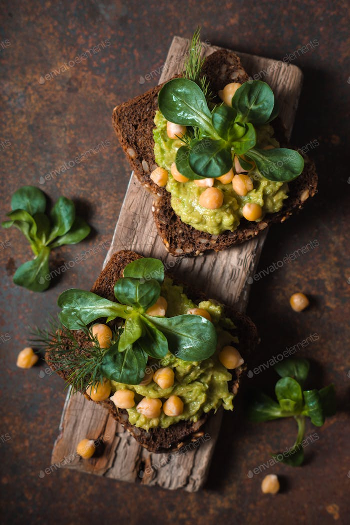 Open sandwich with avocado cream and greens  on the metal background vertical