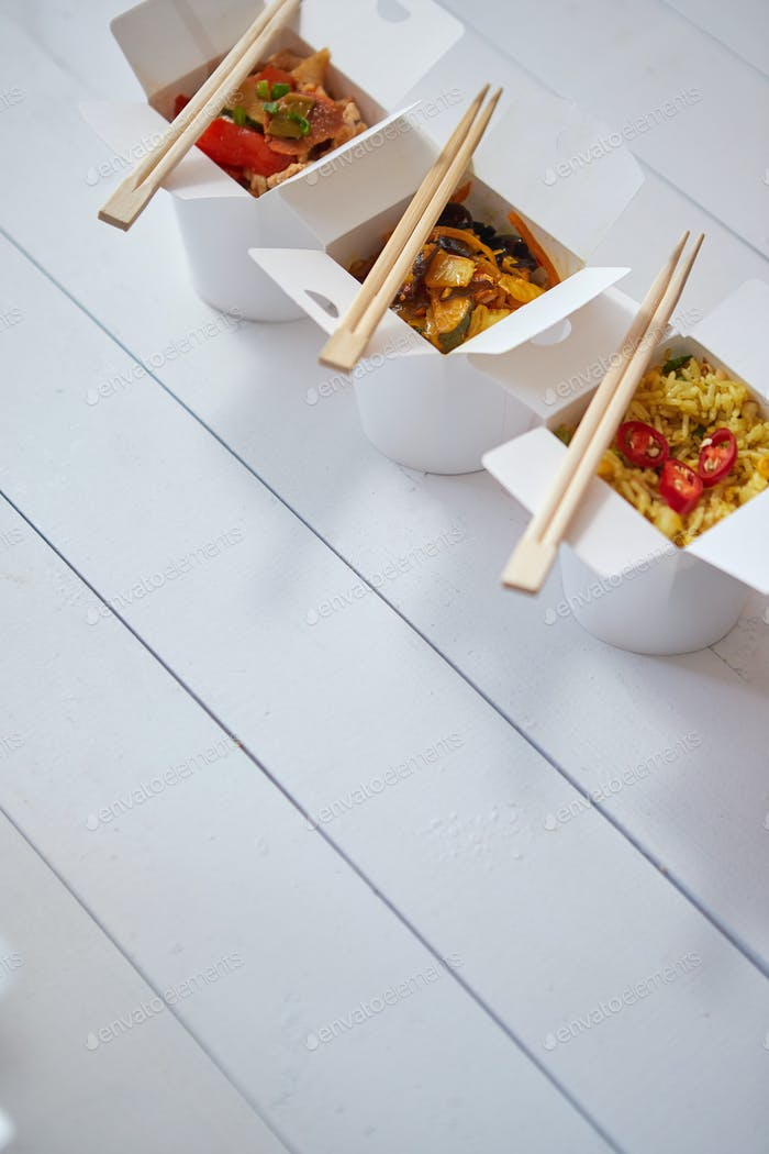 Three take away paper boxes filled with asian food placed in row on white