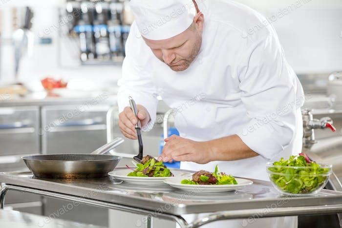 Professioneller Küchenchef bereitet Steakgericht im Restaurant zu
