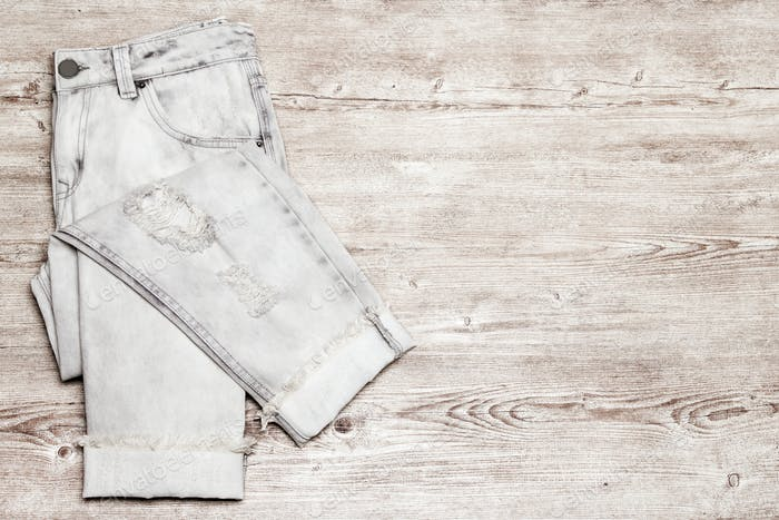 Torn jeans on shabby wooden background with free space for text