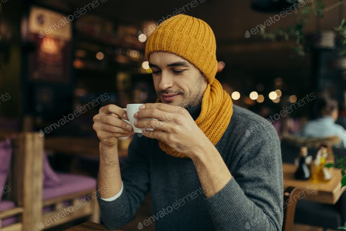Image of handsome young man enjoying coffee in restaurant