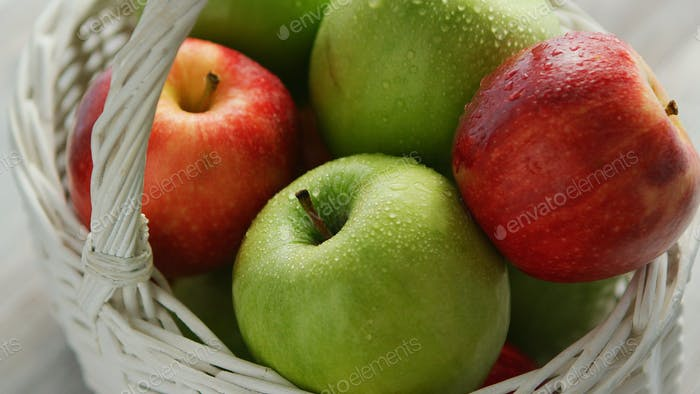 Red and green apples in basket