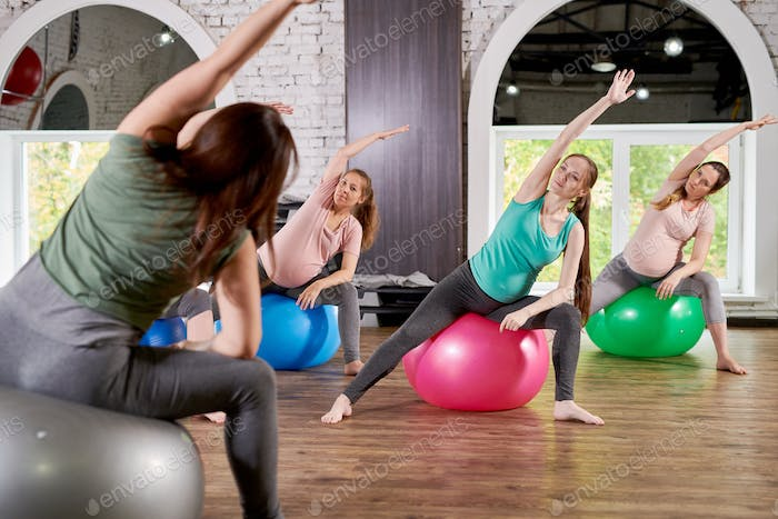 Pregnant Women Stretching in Fitness Class