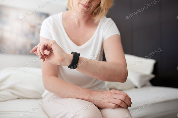 Woman sitting on bed checking time