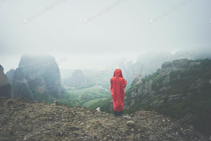 Woman with red raincoat enjoys the view of landscape of Meteora