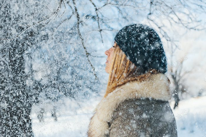 Winter portrait of young beautiful blonde woman covered with sno