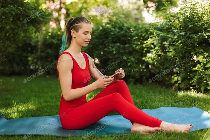 Photo of pretty woman in red jumpsuit sitting and using cellphone on yoga mat while practicing yoga