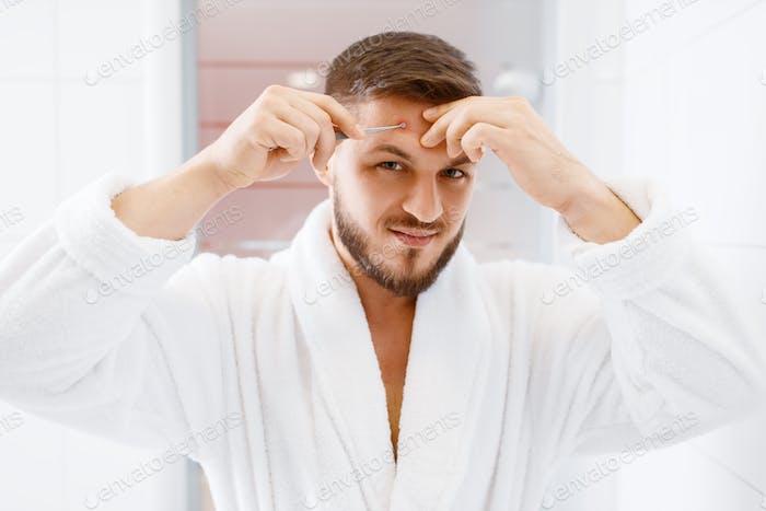 Mann im Bademantel kauterisiert Pickel, Morgenhygiene