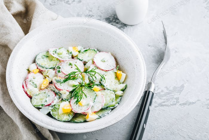 Fresh summer salad with cucumbers, radishes, eggs with cream fresh dressing