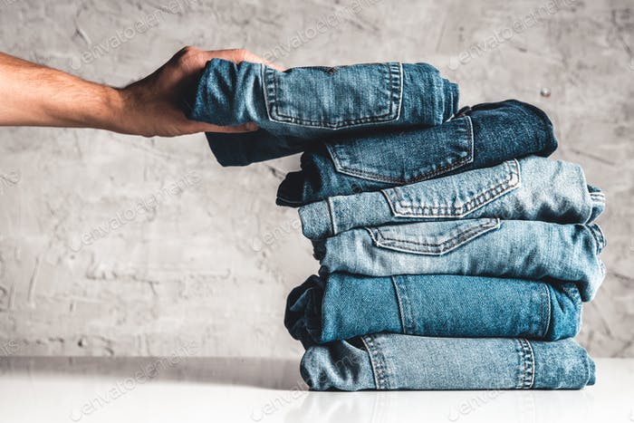 Hands, put the stack of blue jeans on gray background
