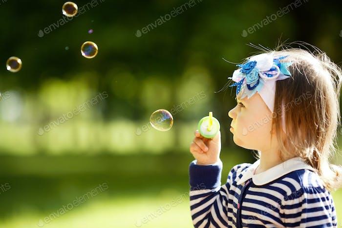 kleines Mädchen spielt mit Blasen
