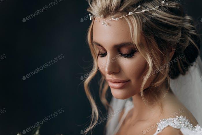 schöne sexy blonde Braut. Posiert im Hochzeitskleid im weißen Zimmer