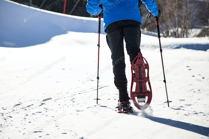 Young man walking in snowshoes over winter background.