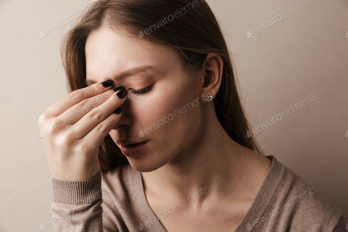Foto von jungen schönen Frau mit Kopfschmerzen Reiben der Stirn