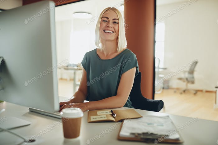 Young businesswoman laughing while working at her office desk
