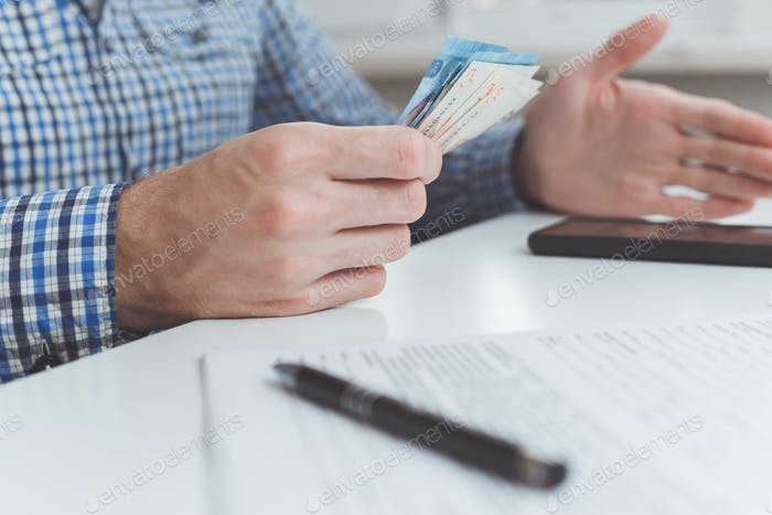 Thumbnail for Tough financial conditions. Businessman holds money and gestures specifically
