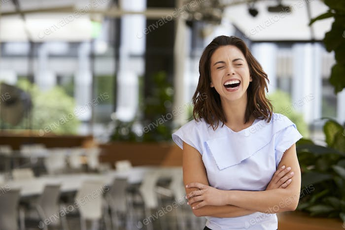 Laughing mixed race young businesswoman with arms crossed